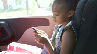 Girl Sitting In Back Seat Of Car Playing With Smartphone