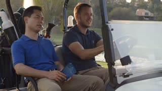 Golfers Driving Buggy Along Golf Course In Slow Motion