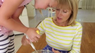 Granddaughter stands on kitchen table adding lemon juice to mixture in bowl.Shot on Canon 5D Mk2 at at a frame rate of 30 fps
