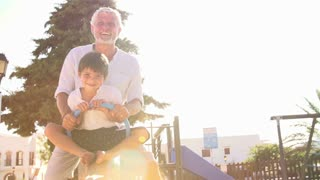 Grandfather And Grandson On Seesaw In Playground