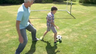 Grandfather And Grandson Playing Football In Garden At Home