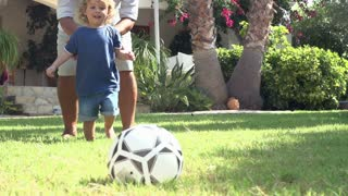 Grandfather Playing Football With Grandson In Garden