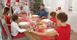 Grandfather says grace as family sit around table holding hands at Christmas meal