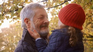 Grandfather Walking With Granddaughter In Autumn Countryside