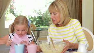 Grandmother and granddaughter sitting at kitchen table as girl adds ingredients to bowl.Shot on Canon 5D Mk2 at at a frame rate of 30 fps