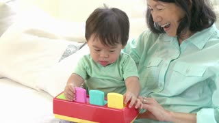 Grandmother And Grandson Playing With Toy Together