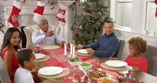Grandmother brings out Christmas turkey to family seated around table for lunch- everybody applauds as Grandfather prepares to carve