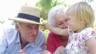 Grandparents And Granddaughter Having Fun In Park Together