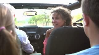 Grandparents Taking Grandchildren On Trip In Open Top Car