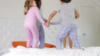 Group Four Children Playing Ring-Around-The-Rosy On Parents Bed