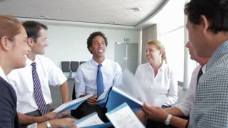 Group Of Businesspeople Discussing Document Together