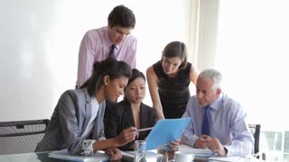 Group Of Businesspeople Having Meeting At Desk In Office