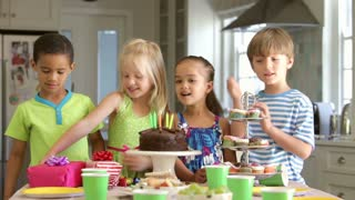 Group Of Children Celebrating Birthday With Cake And Gifts
