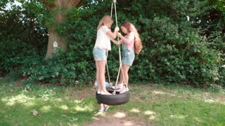 Group Of Children Playing On Tire Swing In Garden