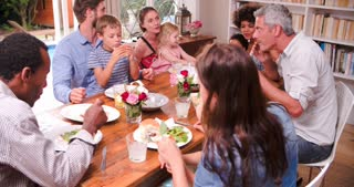 Group Of Families Having Meal At Home Together