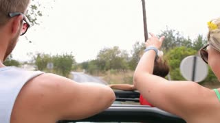 Group Of Friends Dancing In Back Of Open Top Car