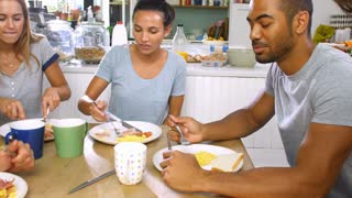Group Of Friends Eating Cooked Breakfast In Kitchen Together