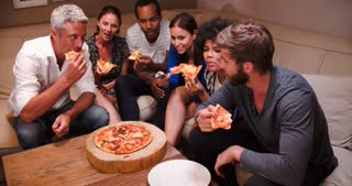Group Of Friends Eating Takeaway Pizza And Watching TV