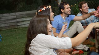 Group Of Friends Enjoying Night Time Party In Garden