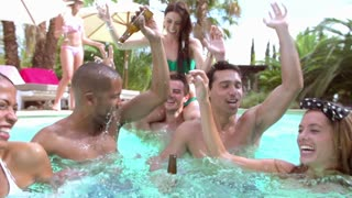 Group Of Friends Having Party In Pool Drinking Champagne