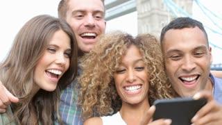 Group Of Friends Taking Selfie By Tower Bridge In London