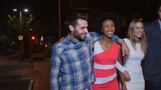 Group Of Friends Walking Along Street On Night Out