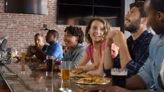 Group Of Friends Watching Game In Sports Bar On Screens