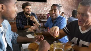 Group Of Male Friends Eating Out In Sports Bar Shot On R3D