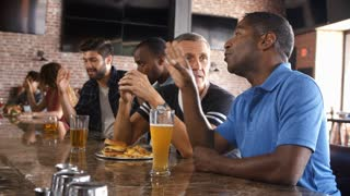Group Of Male Friends Watching Game In Sports Bar