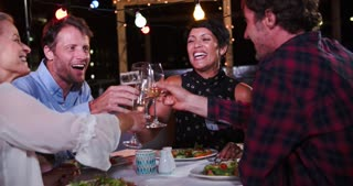 Group Of Mature Friends Enjoying Meal At Rooftop Restaurant
