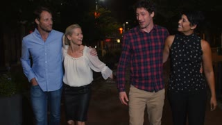 Group Of Mature Friends Walking Along Street On Night Out