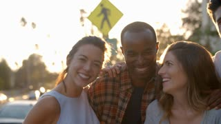 Group of smiling young adult friends embracing in the street