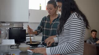 Group Of Students Cooking Meal In Shared House