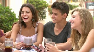 Group Of Teenage Friends Using Mobile Phone Sitting At Caf�