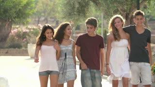 Group Of Teenage Friends Walking Along Street In Slow Motion