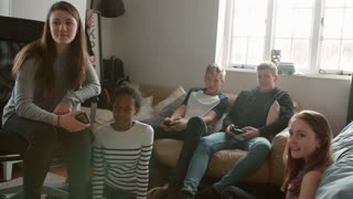 Group Of Teenagers Playing Video Game And Chat In Bedroom