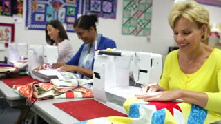Group Of Women Using Electric Machines In Sewing Class