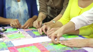 Group Of Women Working On Quilt Together