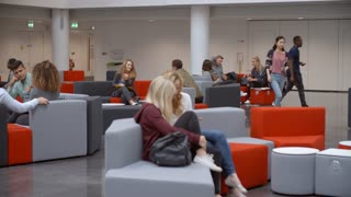 Groups of students socialising in the lobby of a university