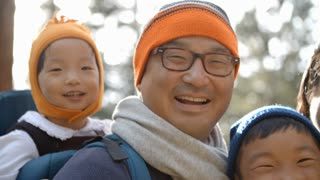 Handheld close up of Asian family of four in a forest