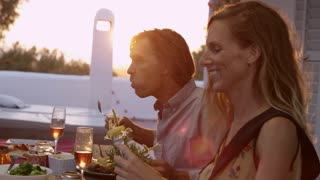 Handheld close up of two couples eating dinner on a terrace, shot on R3D