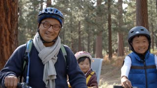 Handheld pan of Asian family on bikes in a forest, close up