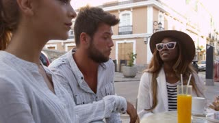 Handheld panning shot of friends at a table outside a cafe, shot on R3D