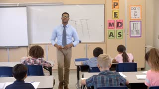 Happy black male teacher walking through class toward camera