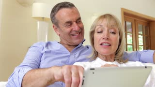 Happy couple relaxing on sofa together as woman holds and operates digital tablet.Shot on Canon 5D Mk2 at at a frame rate of 30 fps
