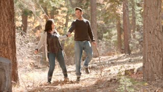 Happy Hispanic couple hold hands walking together in forest