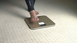 Happy Overweight Woman Standing On Scales In Bedroom
