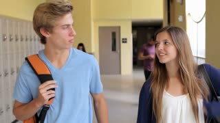 High School Student Couple Walking Along Hallway