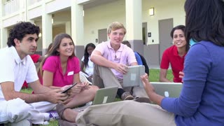High School Students And Teacher Studying Outdoors On Campus