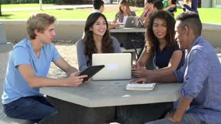 High School Students Collaborating On Project In Playground
